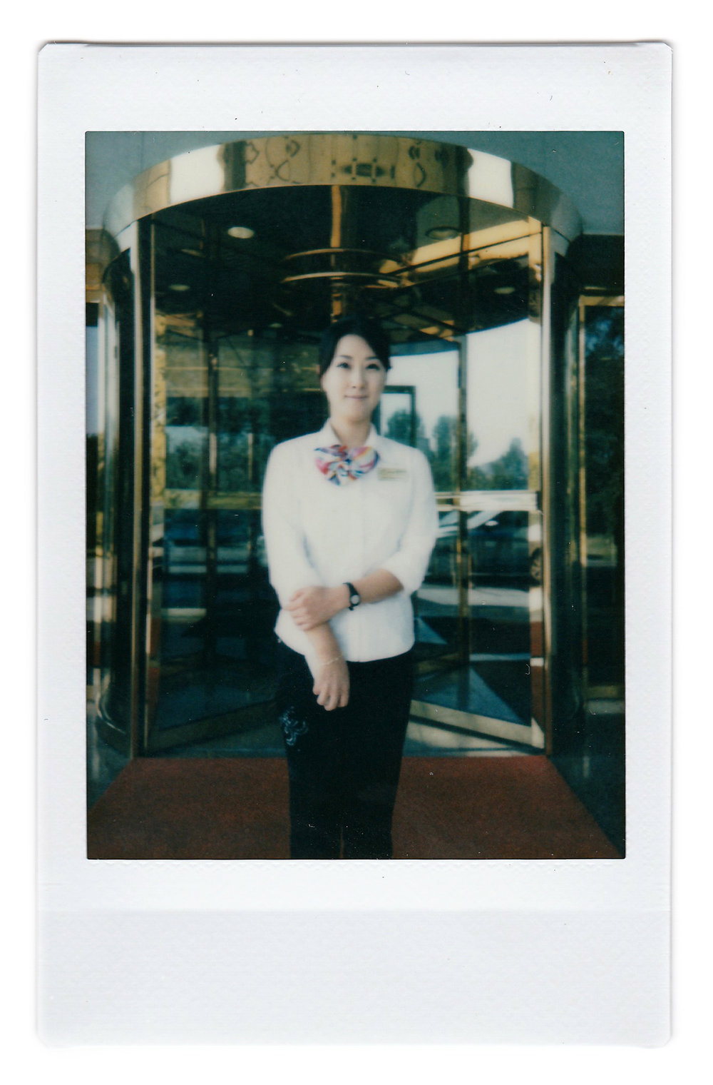 "In this Oct. 14, 2015, photo made with an instant camera, Kil Jin A, 29, poses for a portrait at the entrance of the Pothonggang Hotel where she works with mobile phone service provider Koryolink, in Pyongyang, North Korea. She has been working with Koryolink for 8 years and enjoys her job as a sales executive because it gives her opportunities to meet visitors from abroad. When asked what's important to them, North Koreans might talk about working hard, or doing well at sports, or having a big family, but leader Kim Jong Un is never far from the conversation. Her motto: ""To always help others, but of course, patriotism towards my country is most important."" (AP Photo/Wong Maye-E)"