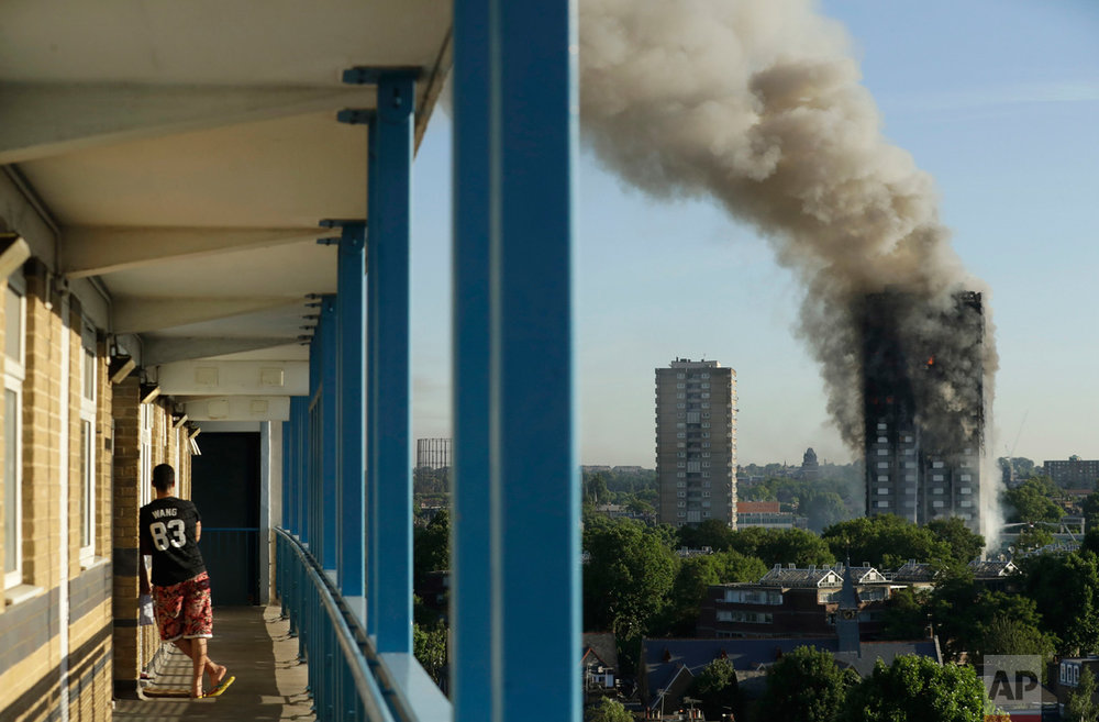 A resident in a nearby building watches smoke rise from a building on fire in London, Wednesday, June 14, 2017. Grief turned to outrage Friday amid reports that materials used in the building's renovation could have fueled the inferno that left dozens dead and missing as it decimated the public housing block. (AP Photo/Matt Dunham)