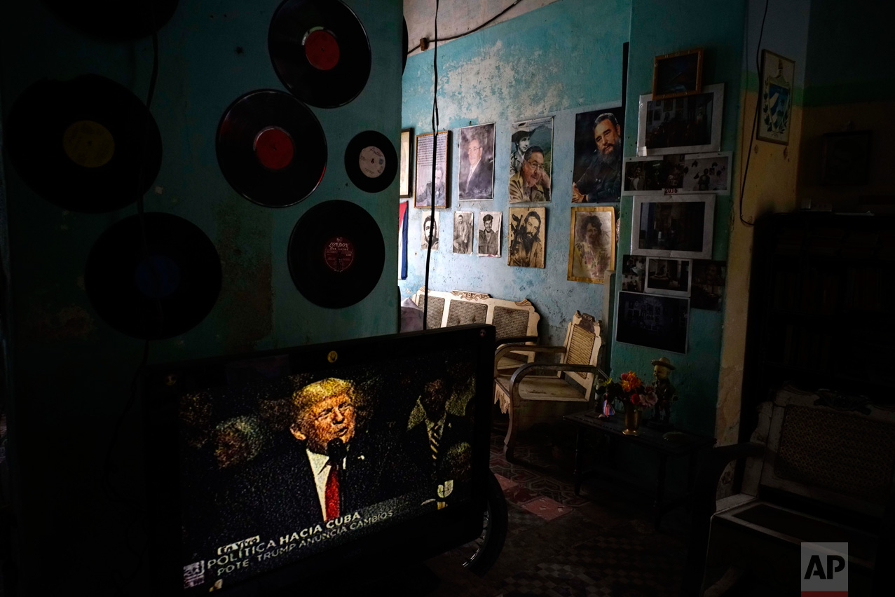 A television set shows U.S. President Donald Trump announcing his new Cuba policy, in a living room decorated with images of Cuban leaders at a house in Havana, Cuba, Friday, June 16, 2017. Trump declared he was restoring some travel and economic restrictions on Cuba that were lifted as part of Barack Obama's historic easing. (AP Photo/Ramon Espinosa)
