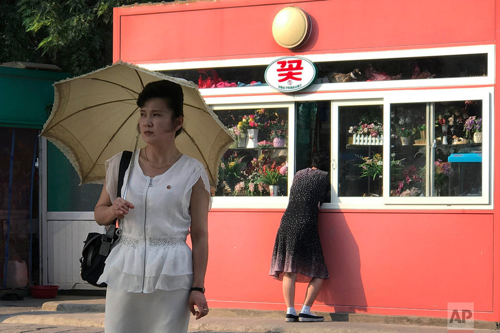 A woman looks into the window of a kiosk selling gifts and flowers in Pyongyang, North Korea, as a pedestrian waits to cross the street on Friday, June 16, 2017. Kiosks like these are a common sight around the city, some also selling food and drinks. (AP Photo/Wong Maye-E)