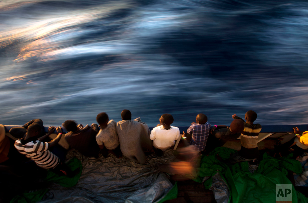 Migrants and refugees stand on the deck of the vessel Golfo Azzurro after being rescued by Spanish NGO Proactiva Open Arms workers on the Mediterranean Sea, Friday, June 16, 2017. A Spanish aid organization Thursday rescued more than 600 migrants who were attempting the perilous crossing of the Mediterranean Sea to Europe in packed boats from Libya. (AP Photo/Emilio Morenatti)