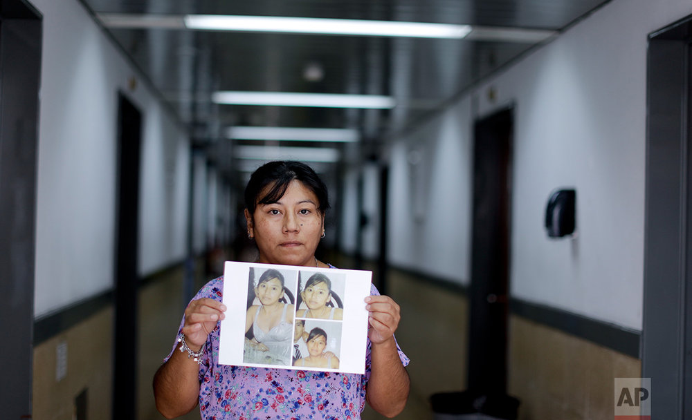In this Feb. 10, 2017 photo, Mercedes Zambrano holds photos of her sister Adriana Marisel, taken on the last day she saw her alive in Buenos Aires, Argentina. Adriana was beaten to death in 2008 by her ex-husband, when a neighbor found the woman's 9-month-old daughter Josefina, breastfeeding from her mother's dead body. The ex-husband was convicted of involuntary manslaughter and sentenced to five years, which he already served. Mercedes said her family lives locked inside their home like prisoners, fearing a new attack, and that they're still trying to get full custody of Josefina, nine years later. (AP Photo/Natacha Pisarenko)