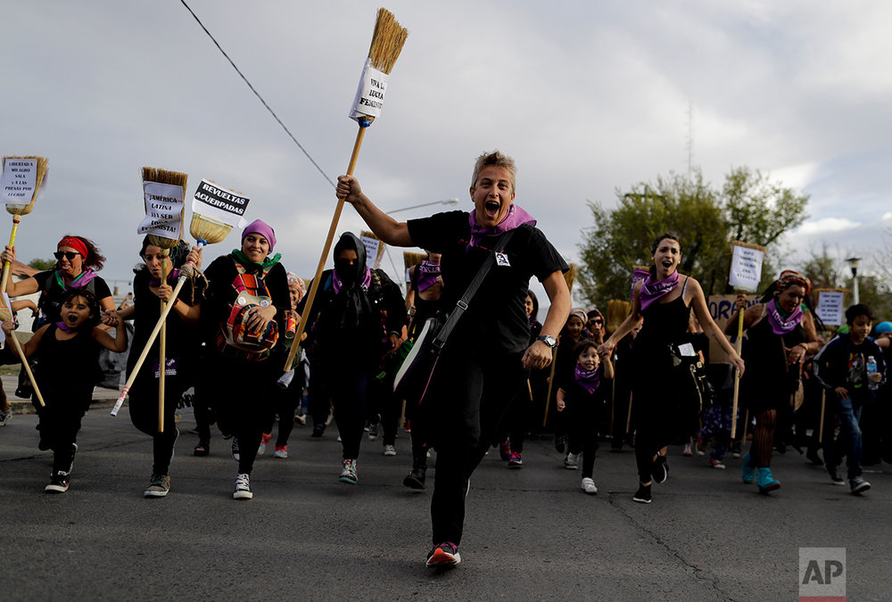"In this March 8, 2017 photo, women run with brooms during an International Women's Day march in Neuquen, Argentina. This year, the ""Ni Una Menos"" movement to protest violence against women helped organize a strike for International Women's Day on March 8. Women from Thailand to Chile and Poland to South Korea, followed them on a day without work. (AP Photo/Natacha Pisarenko)"