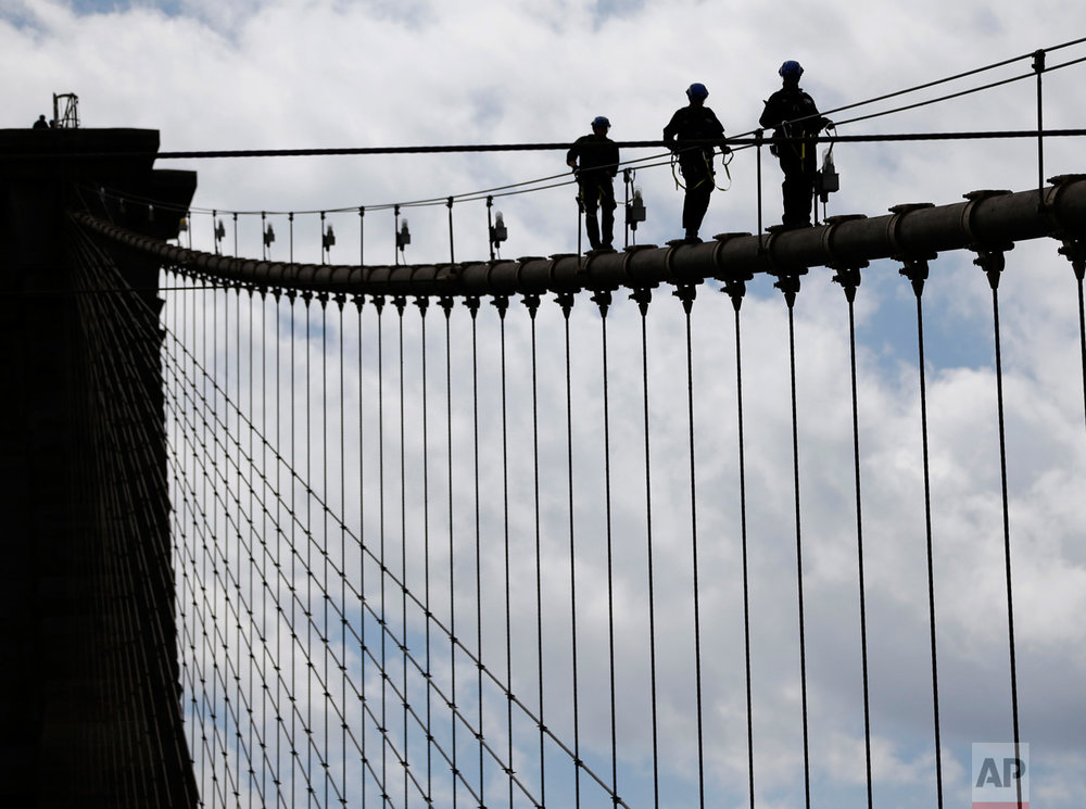 In this Tuesday, May 2, 2017 photo, New York City police officers, including members of the Emergency Services Unit, walk down a cable on the Brooklyn Bridge during a training exercise in New York. The 400-team unit, an elite group of officers trained to handle the city's most dangerous rescues, trains for months not only on technical rescue techniques, but also on how to talk to people to get them down safely. (AP Photo/Seth Wenig)