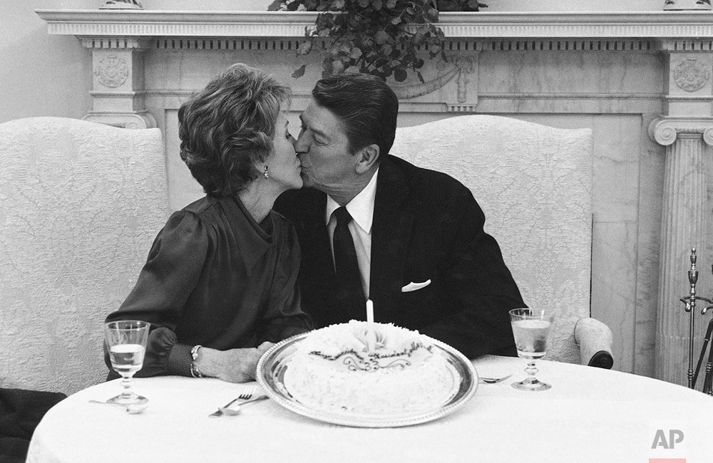 President Ronald Reagan and first lady Nancy Reagan ss at a photo session at the White House in Washington on Monday, March 4, 1985 on the occasion of their 33rd wedding anniversary. President and Mrs. Reagan were married on March 4, 1952 and invited photographers assigned to the White House for a photo with a small cake. (AP Photo/Scott Applewhite)