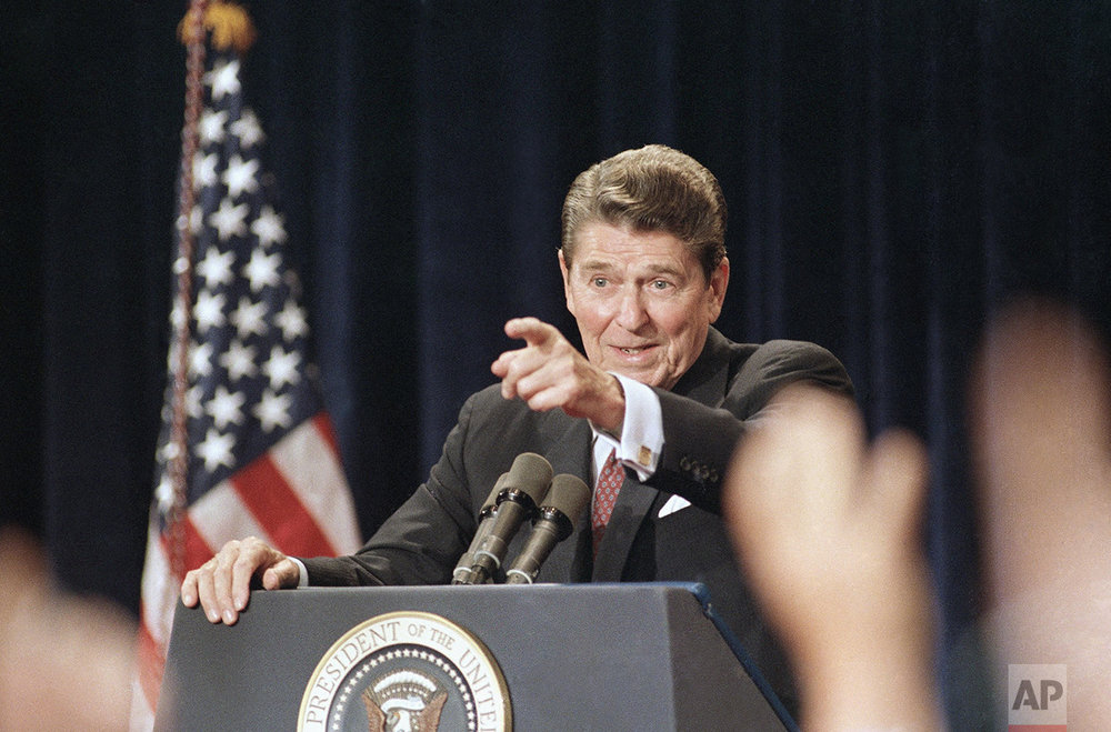 President Ronald Reagan points to raised hands during a rare national address outside the White House on Tuesday, August 12, 1986 in Rosemont, Illinois. (AP Photo/Scott Applewhite)
