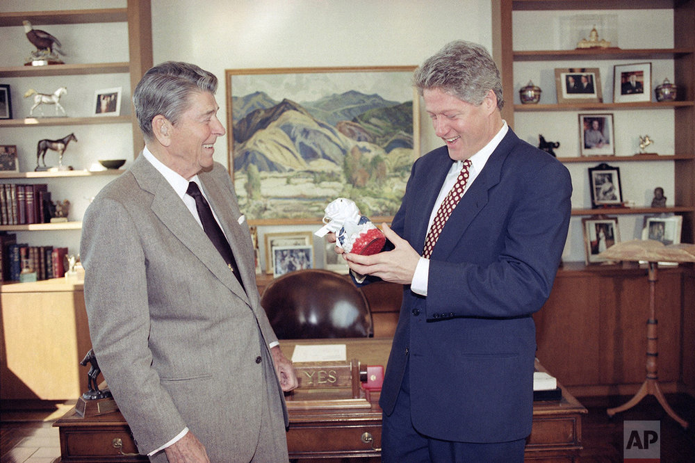 President-elect Bill Clinton reacts as former President Ronald Reagan presents him with a jar of red, white and blue jelly beans at Reagan's office in the Century City section of Los Angeles, Nov. 27, 1992. (AP Photo/J. Scott Applewhite)