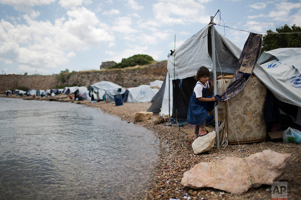 In this June 9, 2017 photo, a little girl from Syria walks on a beach where refugees and other migrants live in makeshift tents near the Souda refugee camp, under the medieval castle of Chios on Chios island, Greece. (AP Photo/Petros Giannakouris)