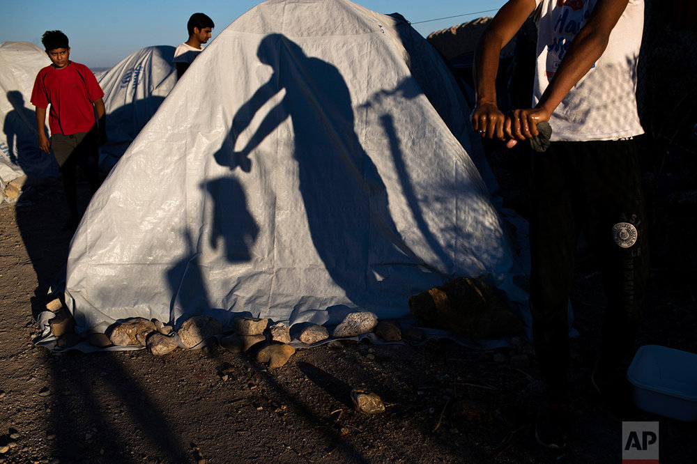 In this June 9, 2017 photo, a Pakistani migrant wrings a t-shirt as his shadow falls on a tent at a beach near the Souda refugee camp, where hundreds refugees and other migrants live in makeshift tents on Chios island, Greece. (AP Photo/Petros Giannakouris)