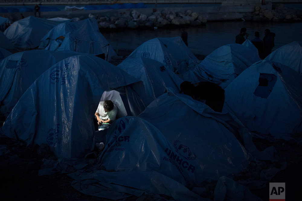 In this June 9, 2017 photo, a refugee looks at his tablet inside a tent that he uses as a shelter at a beach near the Souda refugee camp, on Chios island, Greece. (AP Photo/Petros Giannakouris)