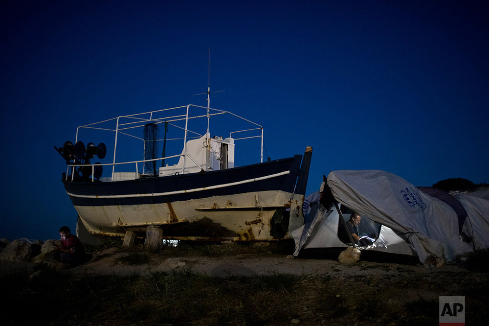 In this June 9, 2017 photo, a refugee chats with his phone inside his shelter that stands next to a fishing boat near the Souda refugee camp, on Chios island, Greece. (AP Photo/Petros Giannakouris)