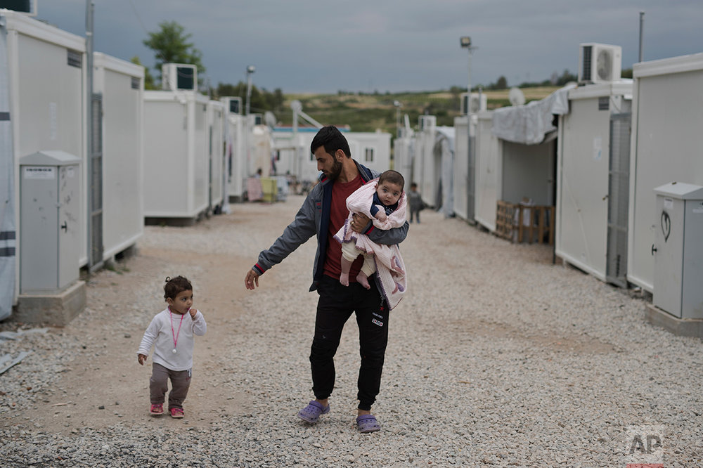 In this May 29, 2017 photo, Barzan Hasan from Irbil, Syria, holds his 5-month-old baby girl Gaylan, as he walks next to his other daughter Lamar on their way to their shelter at the refugee camp of Ritsona about 86 kilometers (53 miles) north of Athens. The family has been stuck in Greece for almost one year and a half, Gaylan was born as a refugee in Greece. (AP Photo/Petros Giannakouris)