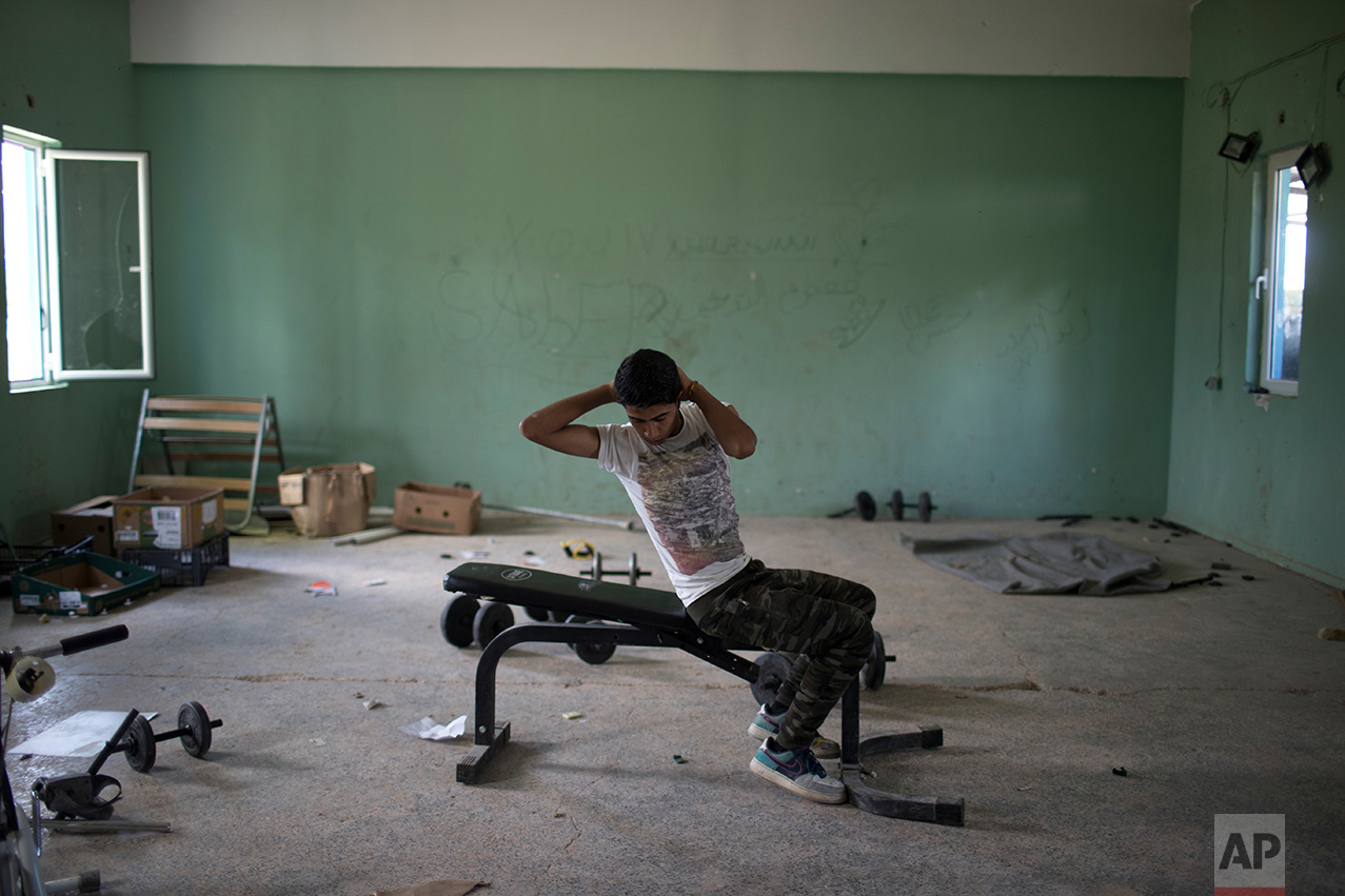 In this May 26, 2017 photo, 16-year- old Amor Biro from Syria works out at the refugee camp of Ritsona about 86 kilometers (53 miles) north of Athens. Amor and his family wants to go to Germany. (AP Photo/Petros Giannakouris)