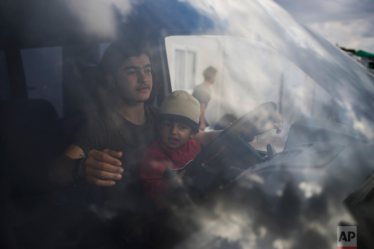 In this May 26, 2017 photo, a Syrian man with a boy drives a van as he distributes food inside the refugee camp of Ritsona about 86 kilometers (53 miles) north of Athens. (AP Photo/Petros Giannakouris)