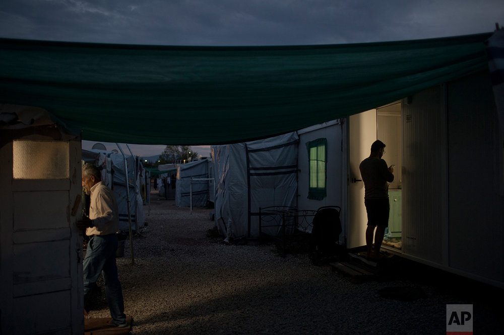 In this May 25, 2017 photo, refugees enter their shelters at the refugee camp of Ritsona about 86 kilometers (53 miles) north of Athens. (AP Photo/Petros Giannakouris)