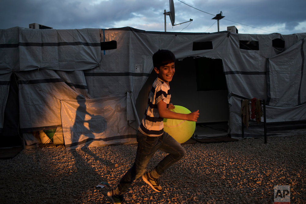 In this May 29, 2017 photo, a Syrian boy runs as he carries a giant tennis ball at the refugee camp of Ritsona about 86 kilometers (53 miles) north of Athens. (AP Photo/Petros Giannakouris)
