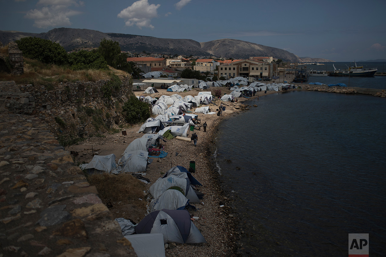 In this June 9, 2017 photo, tents that refugees and other migrants use as a temporary shelter stand on a beach near the Souda refugee camp, next to the medieval castle of Chios island, Greece.  (AP Photo/Petros Giannakouris)
