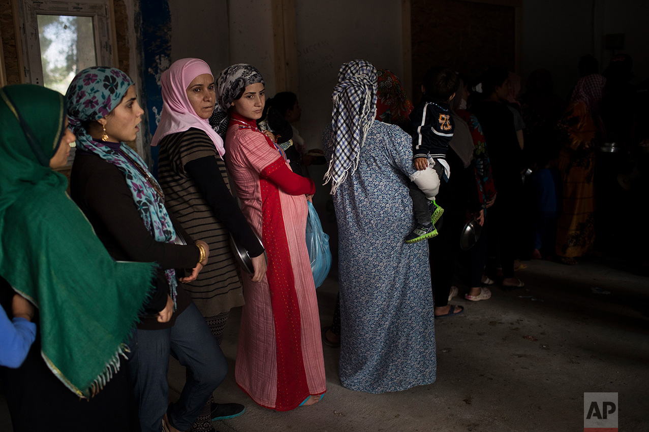 In this May 29, 2017, photo Syrian women queue for food distribution at the refugee camp of Ritsona about 86 kilometers (53 miles) north of Athens. (AP Photo/Petros Giannakouris)