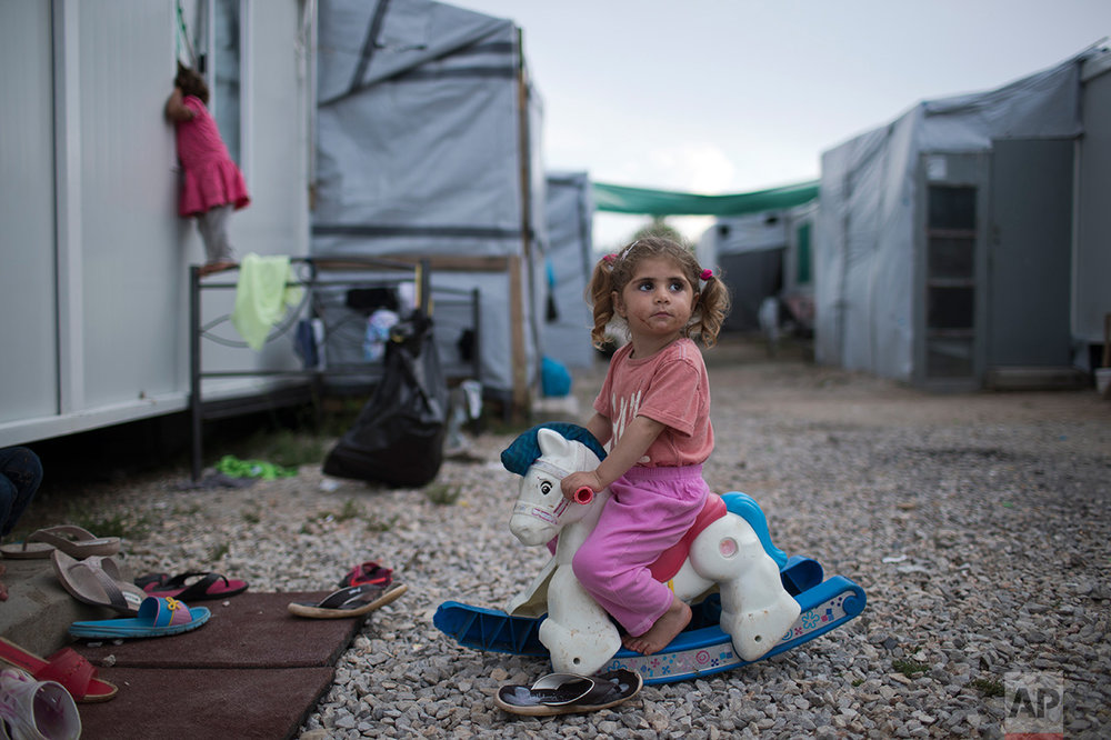 In this May 25, 2017 photo, three-year-old Ragika from Syria plays with a plastic toy horse at the refugee camp of Ritsona about 86 kilometers (53 miles) north of Athens. According to the UN Refugee agency there are more than 21 millions refugees around the world. (AP Photo/Petros Giannakouris)