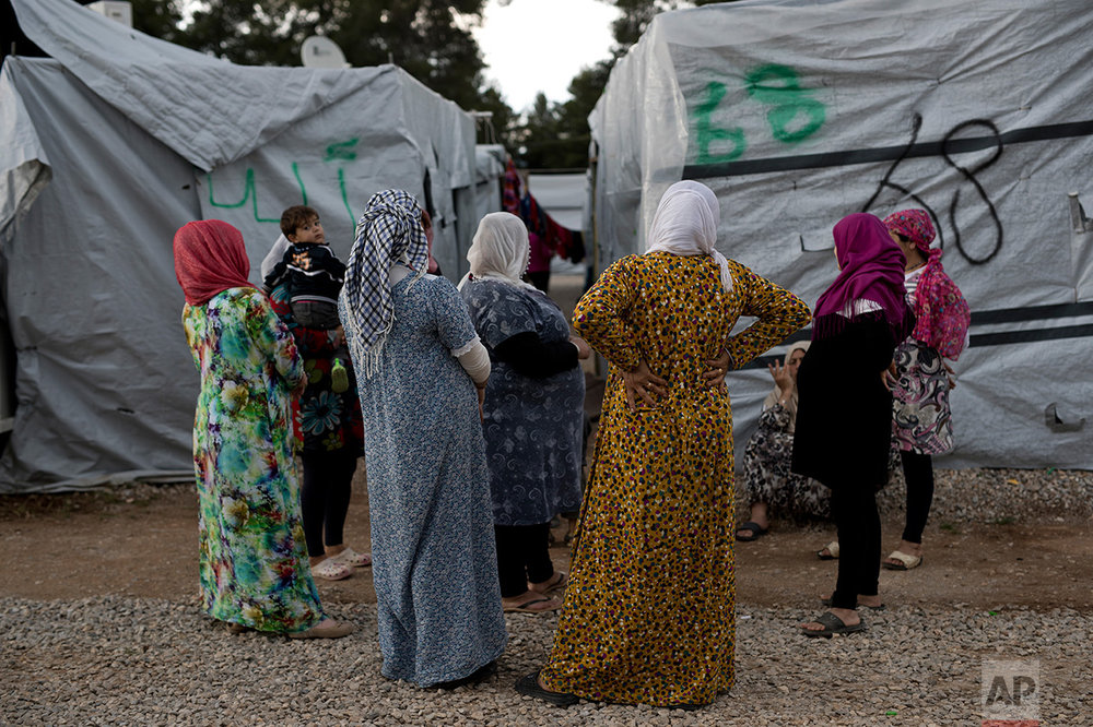 In this May 29, 2017 photo, Syrian women chat at the refugee camp of Ritsona about 86 kilometers (53 miles) north of Athens. 62258 refugees and migrants live in Greece according to the government's latest report on June 18, 2017. (AP Photo/Petros Giannakouris)