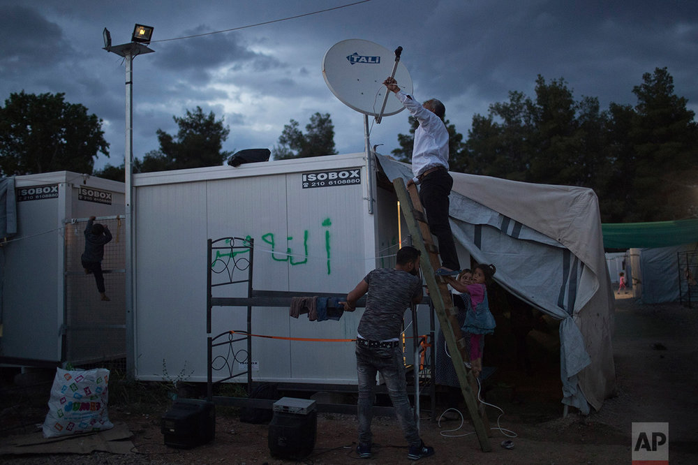 In this May 26, 2017 photo, refugees try to connect a cable to a satellite dish as a child climbs on an iron fence at the refugee camp of Ritsona about 86 kilometers (53 miles) north of Athens. On the mainland, migrant children receive after-hours classes at Greek state schools, while their families are moving out of tent camps and into trailers and subsidized apartments. (AP Photo/Petros Giannakouris)