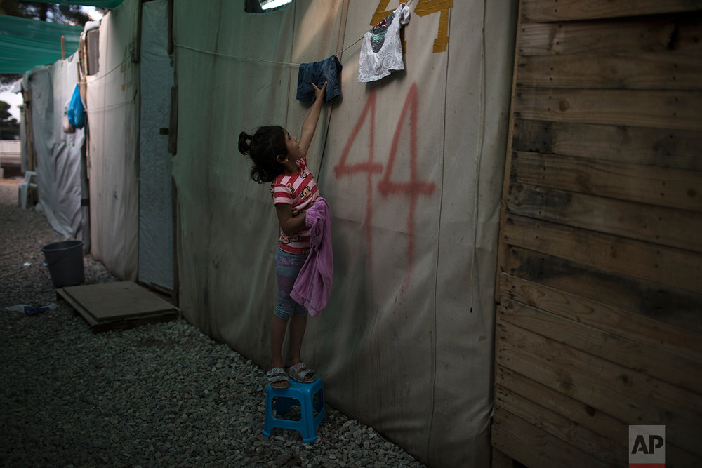 In this May 25, 2017 photo, a Syrian girl takes down dry washing at the refugee camp of Ritsona about 86 kilometers (53 miles) north of Athens. (AP Photo/Petros Giannakouris)