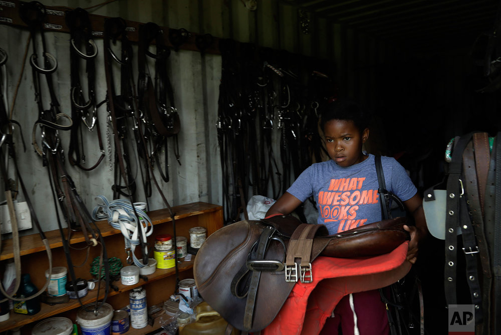 In this Saturday, March 4, 2017 photo, 12 year-old girl Omphile Mashile carries a saddle pad at the Soweto Equestrian Centre in Johannesburg, South Africa. (AP Photo/Themba Hadebe)