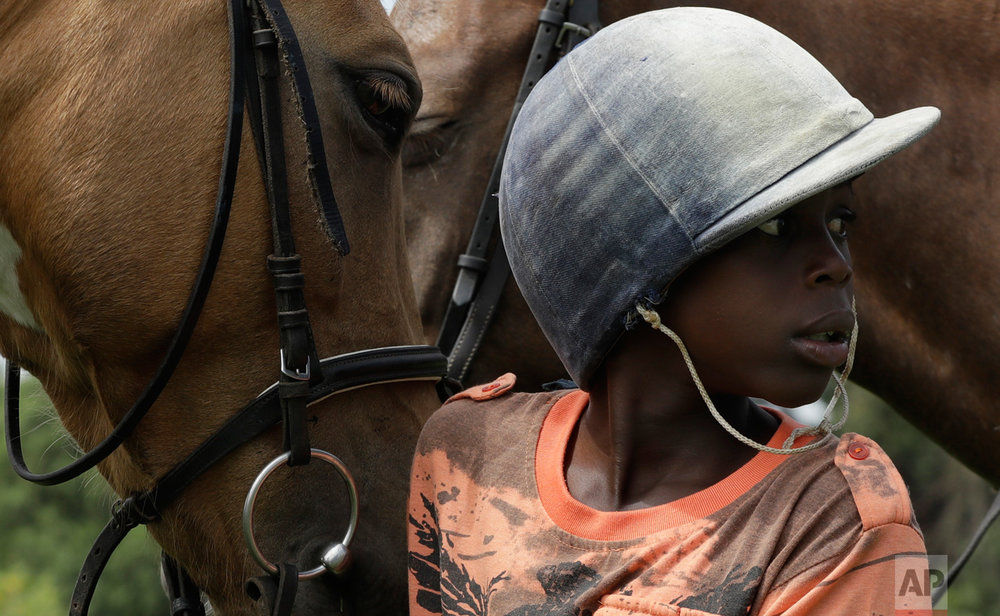 In this Saturday, March 4, 2017 photo, 11 year-old boy Lesekgo Mngadi looks on as he prepares to ride at the Soweto Equestrian Centre in Johannesburg, South Africa. (AP Photo/Themba Hadebe)