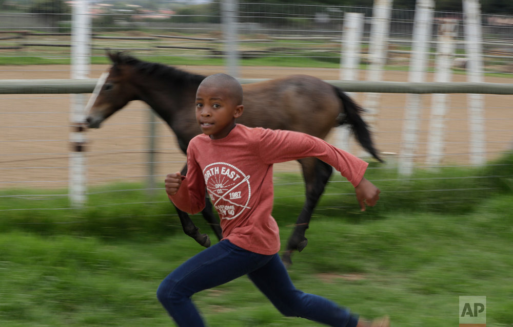 In this Saturday, Feb. 11, 2017 photo, 10 year-old boy Junior Mashile runs as he prepares to ride a horse during a vaulting practice at the Soweto Equestrian Centre in Johannesburg, South Africa. (AP Photo/Themba Hadebe)