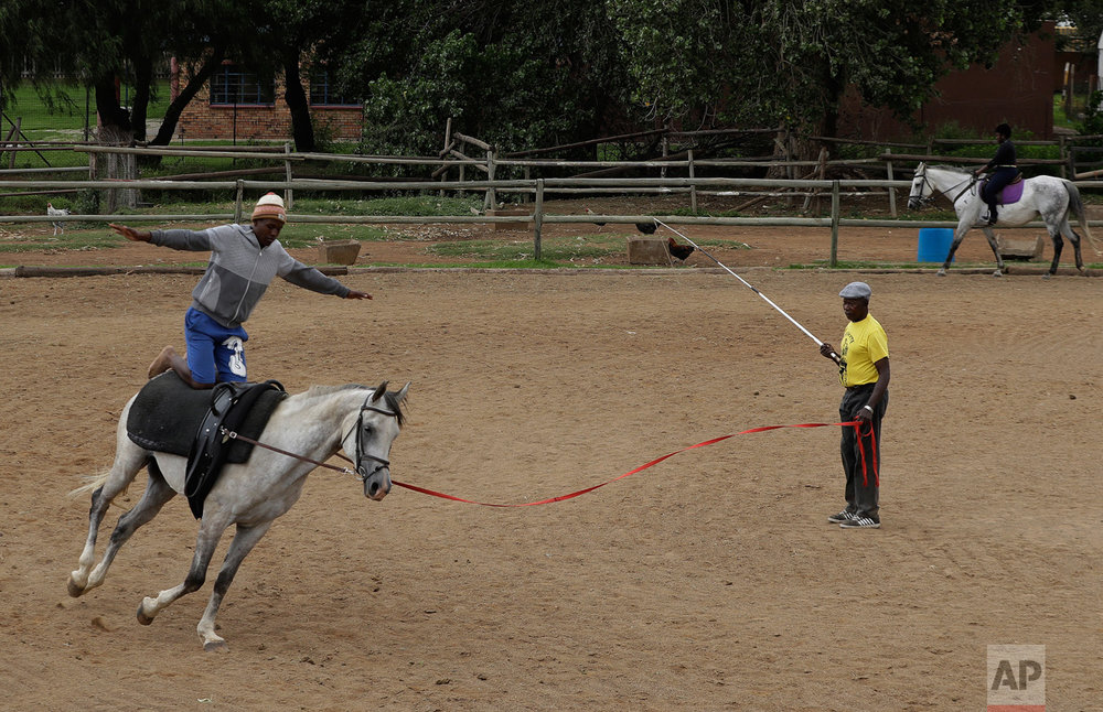 In this Saturday, Feb. 18, 2017 photo, Yanga Ntsume is watched by Enos Mafokate during the equestrian vaulting practice at the Soweto Equestrian Centre in Johannesburg, South Africa. (AP Photo/Themba Hadebe)