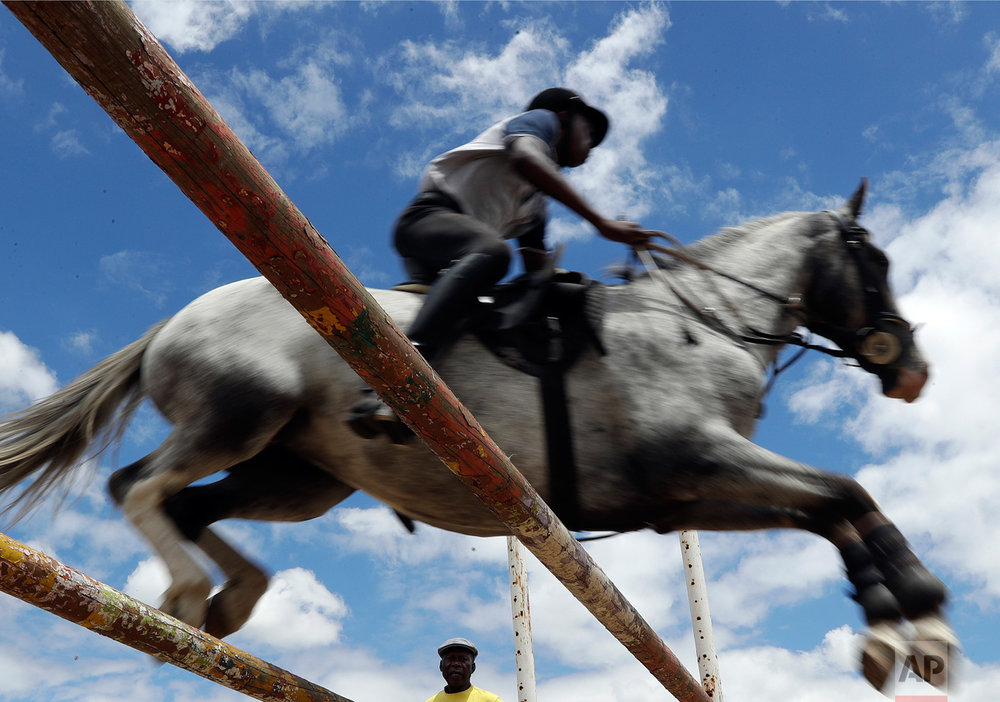 In this Saturday, Feb. 18, 2017 photo, 16-year-old boy Nhlanhla Vilakazi clears a fence with a horse against a blue sky as the trainer Enos Mafokate, watches on during practice at the Soweto Equestrian Centre in Johannesburg, South Africa. (AP Photo/Themba Hadebe)