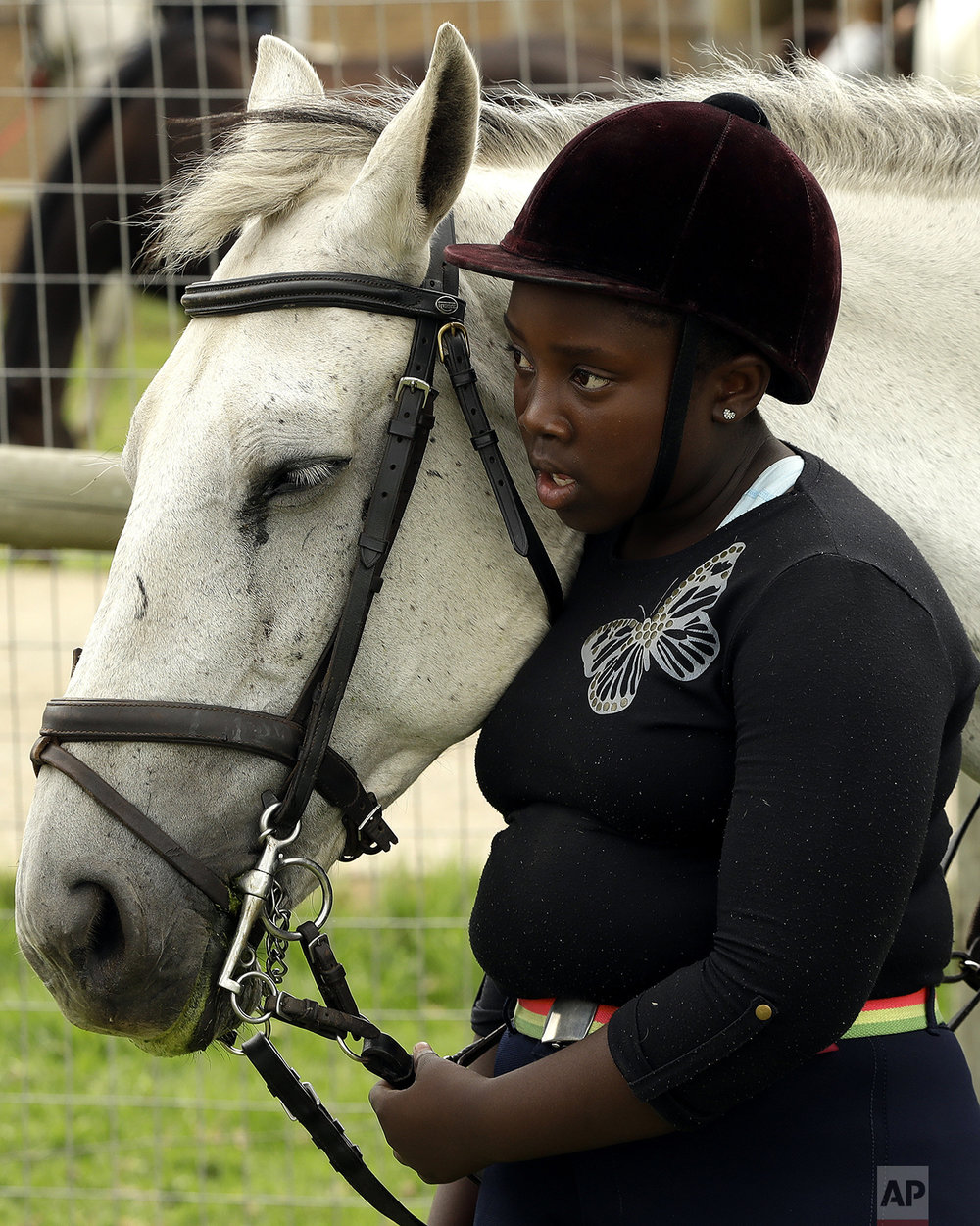 "In this Saturday, Feb. 18, 2017 photo, 13-year-old girl Naledi Mokoena stands with a horse called ""Vuka Zenzele"" during the equestrian vaulting practice at the Soweto Equestrian Centre in Johannesburg, South Africa. (AP Photo/Themba Hadebe)"