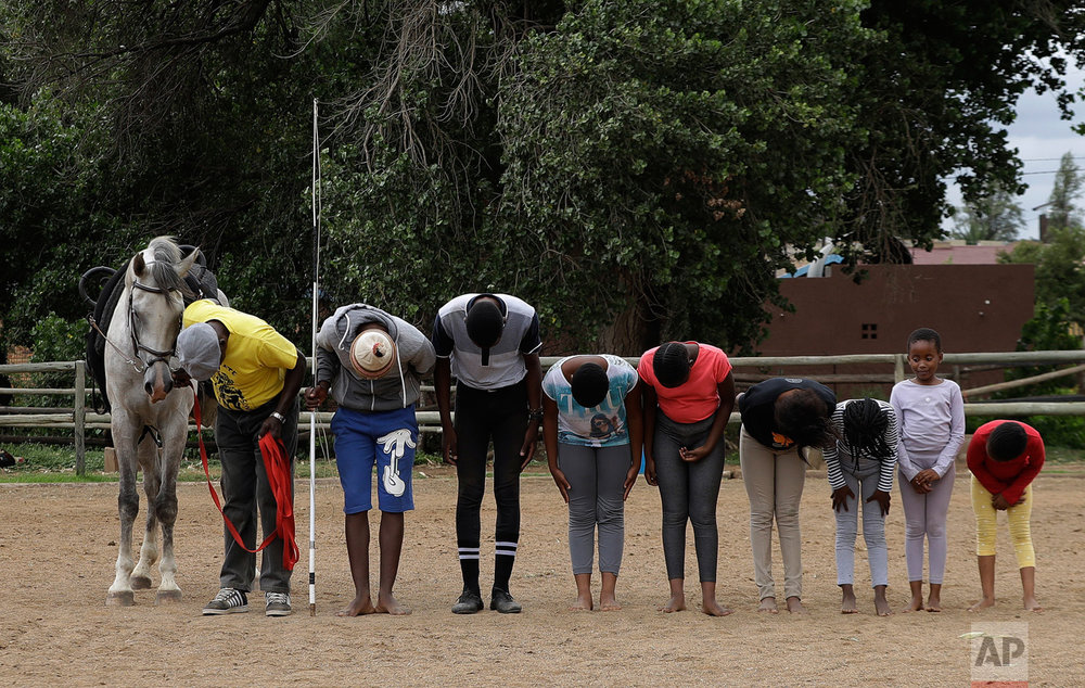 "In this Saturday, Feb. 18, 2017 photo, Enos Mafokate and children gesture to a horse call ""Vuka Zenzele"" at the end of their equestrian vaulting practice at the Soweto Equestrian Centre in Johannesburg, South Africa. (AP Photo/Themba Hadebe)"