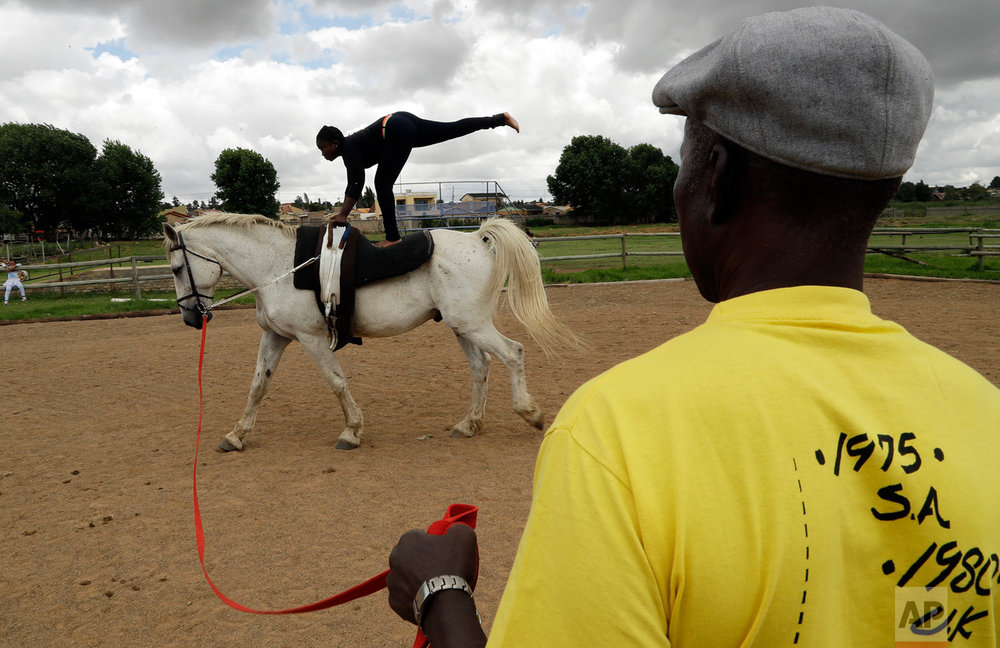 In this Saturday, Feb. 18, 2017, 13-year-old girl Naledi Mokoena is watched by Enos Mafokate during the equestrian vaulting practice at the Soweto Equestrian Centre in Johannesburg, South Africa. The respect displayed at Mafokate's equestrian center in Soweto is a far cry from the tensions under South Africa's previous apartheid system of racial discrimination that erupted into violence more than 40 years ago Friday, when dozens of protesting black students were killed by security forces in the 1976 Soweto uprising. (AP Photo/Themba Hadebe)