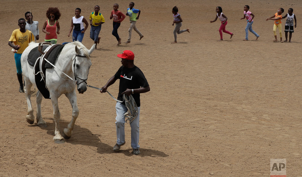 In this Saturday, Feb. 11, 2017 photo, Enos Mafokate leads children during the equestrian vaulting practice at the Soweto Equestrian Centre in Johannesburg, South Africa. The respect displayed at Mafokate's equestrian center in Soweto is a far cry from the tensions under South Africa's previous apartheid system of racial discrimination that erupted into violence more than 40 years ago Friday, when dozens of protesting black students were killed by security forces in the 1976 Soweto uprising. (AP Photo/Themba Hadebe)