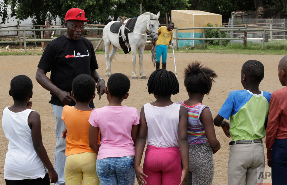 In this Saturday, Feb. 11, 2017 photo, Enos Mafokate speaks to children during an equestrian vaulting practice at the Soweto Equestrian Centre in Johannesburg, South Africa. The respect displayed at Mafokate's equestrian center in Soweto is a far cry from the tensions under South Africa's previous apartheid system of racial discrimination that erupted into violence more than 40 years ago Friday, when dozens of protesting black students were killed by security forces in the 1976 Soweto uprising. (AP Photo/Themba Hadebe)