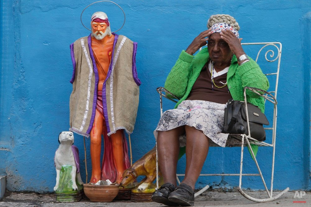 """Esilda Espinosa sits next to a statue of the Catholic saint Lazaro, as she waits for a passersby to donate alms that she will use to finance a celebration on the saint's feast day in Havana, Cuba, Friday, Dec. 7, 2012. Affectionately known as """"El Viejo Lazaro,"""" or the Santeria equivalent, Babalu Aye, the religious icon is usually represented wearing ragged clothes and with dogs licking the sores on his feet. Both the Catholic saint and the Santeria Orisha are associated with suffering and disease and are honored by their devotees on Dec. 17. (AP Photo/Franklin Reyes)"""