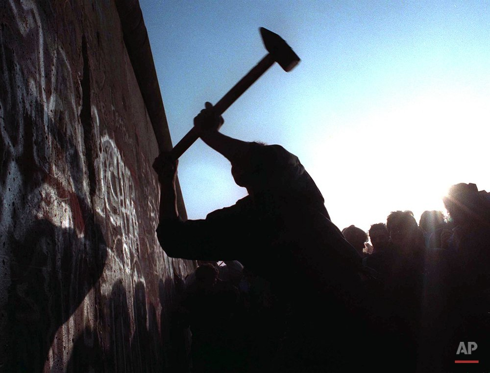 A man hammers away at the Berlin Wall on Nov. 12, 1989 as the border barrier between East and West Germany was torn down after 28 years, symbolically ending the Cold War.  (AP Photo/John Gaps III)