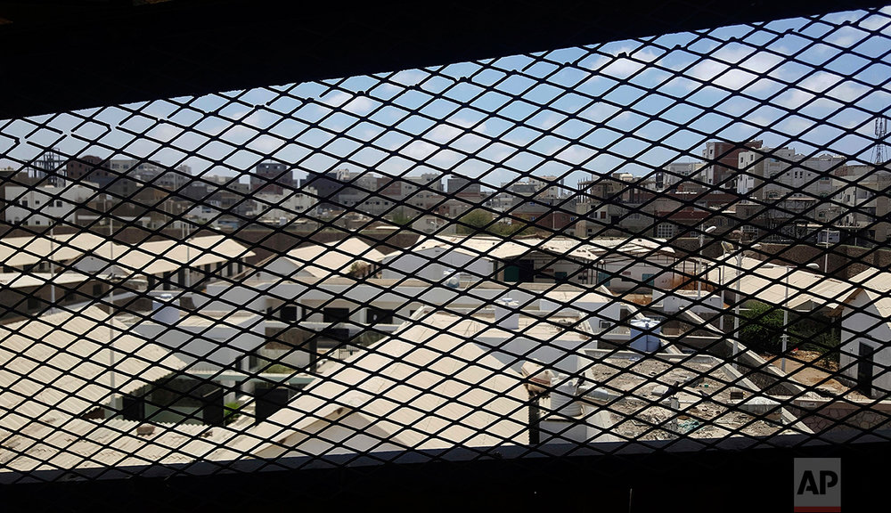 A view through a mesh window looks out over part of Aden Central Prison, known as Mansoura.