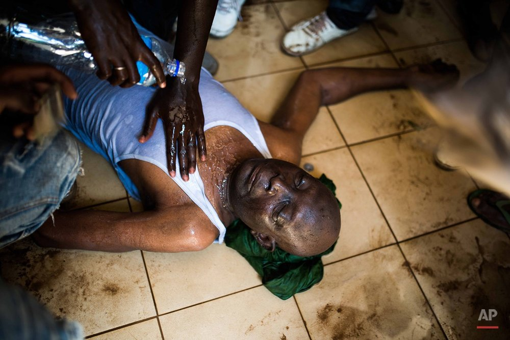 Protestors  pour  water on a  injured man near the parliament building in Burkina Faso as people protest  against their longtime president Blaise Compaore who is seeking another term in Ouagadougou, Burkina Faso, Thursday, Oct. 30, 2014. Protesters stormed Burkina Faso's parliament Thursday, dragging furniture and computers onto the street and setting the main chamber ablaze, in the most significant challenge to the president's rule during his 27 years in power.(AP Photo/Theo Renaut)