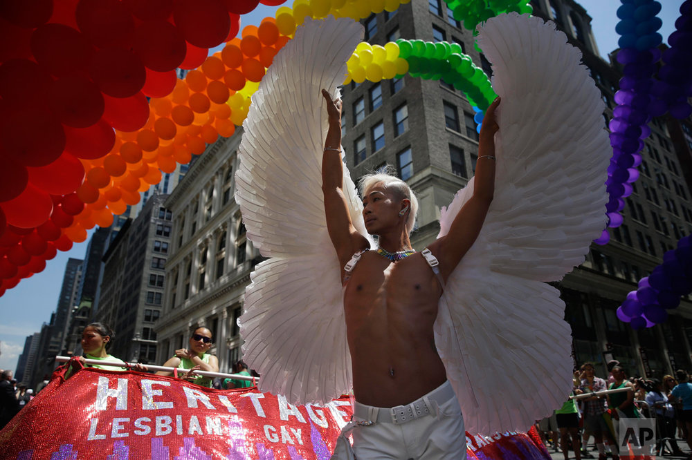 Kent Chua poses for pictures at the start of the Gay Pride Parade in New York, Sunday, June 29, 2014. (AP Photo/Seth Wenig)