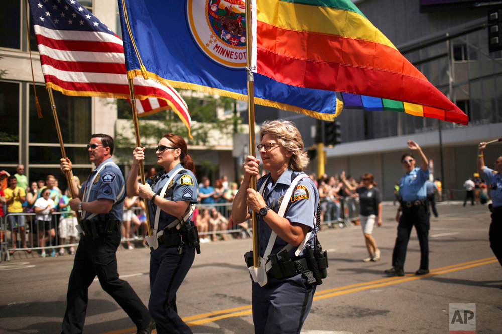 In this June 28, 2017 photo, officers from Minneapolis and St. Paul police departments lead the the Twin Cities Pride Parade in Minneapolis.   Organizers of Sunday, June 25, 2017  Twin Cities Pride Parade asked the police department to limit participation following the acquittal of police officer Jeronimo Yanez in the death of Castile. The openly gay police chief said the decision was divisive and hurtful to LGBT officers, which the organizers acknowledged. (Jeff Wheeler/Star Tribune via AP)