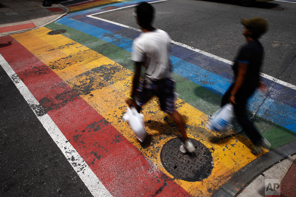 In this June 17, 2016, photo, people walk across a rainbow crosswalk painted in support of the LGBT community in the Gayborhood, a gay-friendly section of Philadelphia. The Philadelphia Commission on Human Relations recommended Monday, Jan. 23, 2017, that bars and nonprofit organizations in Philadelphia's gay neighborhood undergo training for racial bias and hire more diverse staff, after a new city report found women, minorities and transgender people have felt unwelcome and unsafe in the Gayborhood for decades. (AP Photo/Matt Rourke)