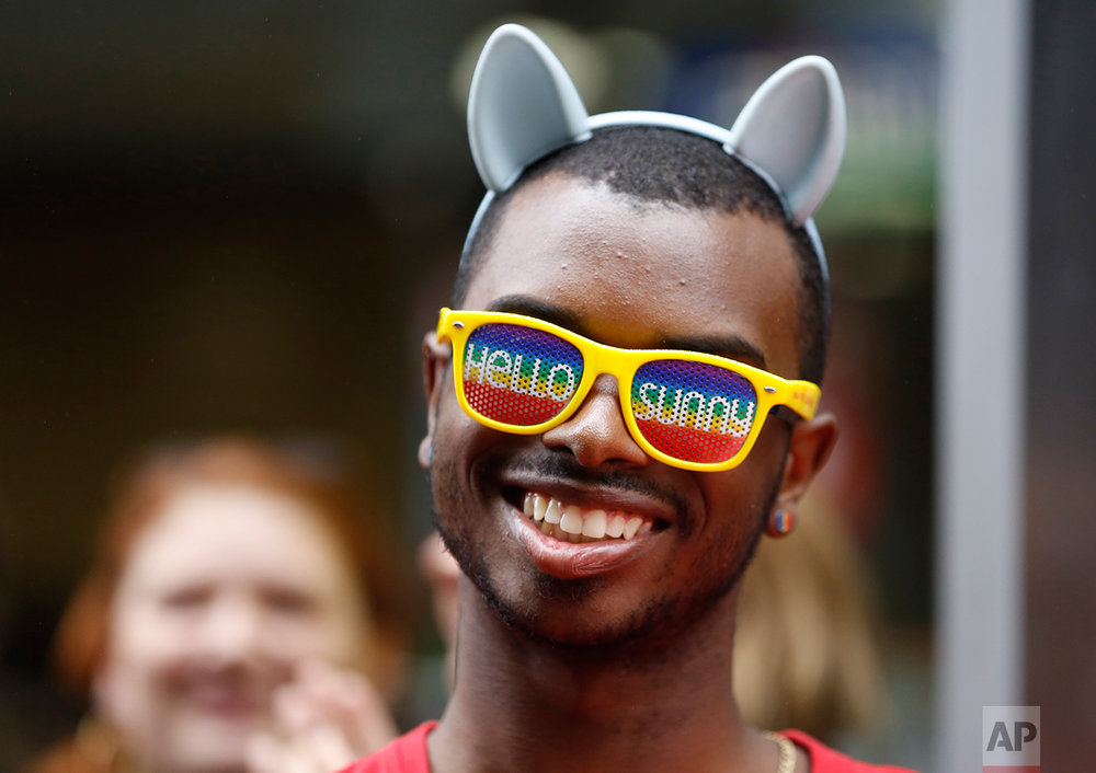 "Julian Sims, of Meriden, Conn., wears ""Hello Sunny"" glasses and rainbow-colored earrings as he watches floats and people parade down New York's Fifth Avenue during the Heritage Pride March in New York, June 28, 2015. (AP Photo/Kathy Willens)"