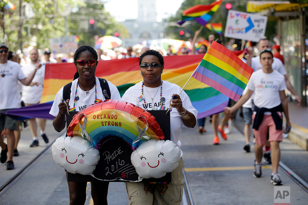 Chanta Anderson, right, and Ashlee Stephens hold signs in memory of the Orlando nightclub shooting during the San Francisco Gay Pride parade Sunday, June 26, 2016, in San Francisco. (AP Photo/Marcio Jose Sanchez)
