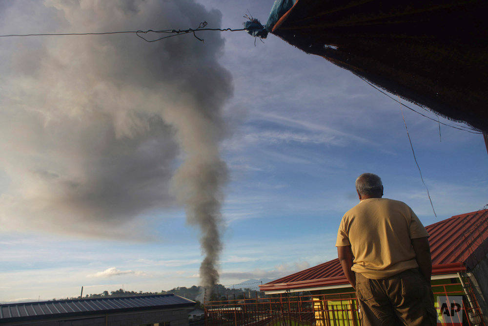 A man looks at a burning structure during early morning airstrikes by government forces in the continuing fight for Marawi city by Muslim militants Friday, June 23, 2017, in southern Philippines. The siege by militants aligned with the Islamic State group continues as it enters its second month Friday. (AP Photo/Linus Guardian Escandor II)