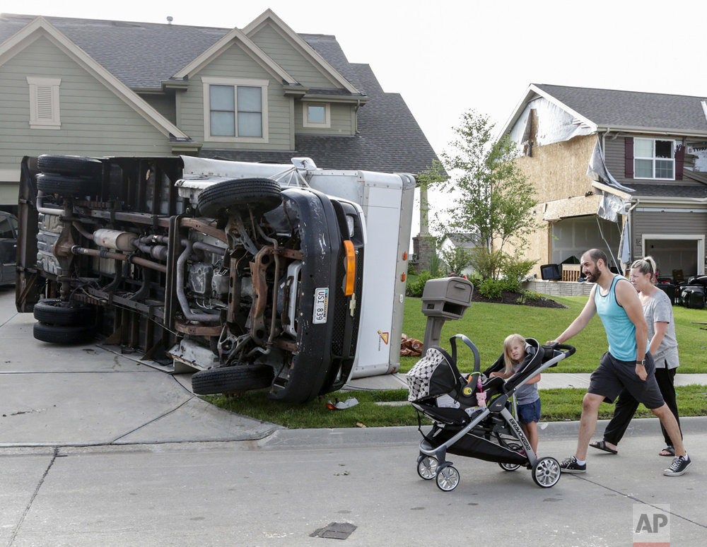Vincent and Lindsey Mercado and their children walk past an overturned truck and weather-damaged homes in the Hyda Hills neighborhood in Bellevue, Neb., Saturday, June 17, 2017. A severe weather front passed through the area the previous evening. (AP Photo/Nati Harnik)