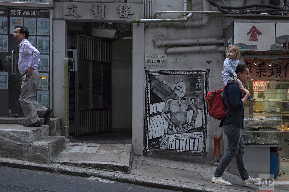 In this May 20, 2017, photo, people walk on the slope in Central district, Hong Kong. (AP Photo/Kin Cheung)