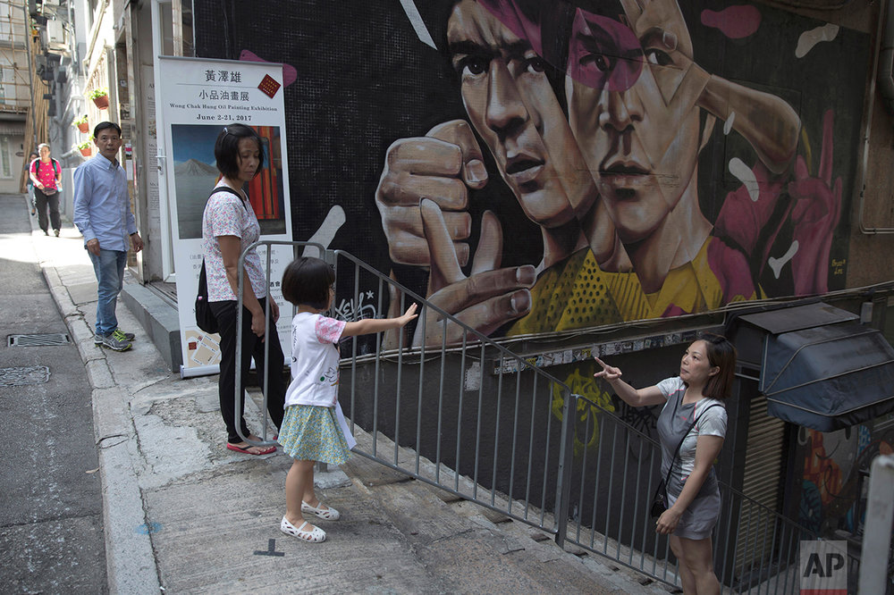 In this June 7, 2017, photo, a mother and daughter play on stairs with wall painting of martial arts star Bruce Lee in the background, in Central district, Hong Kong. (AP Photo/Kin Cheung)