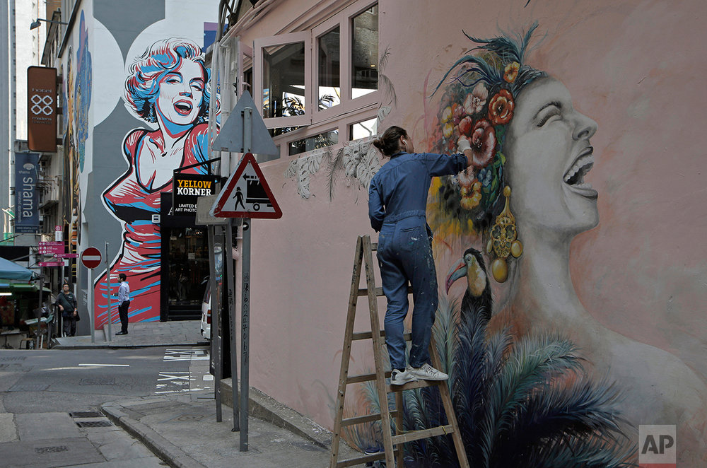 In this March 2, 2017 photo, a woman draws on wall in Central district, Hong Kong. (AP Photo/Kin Cheung)